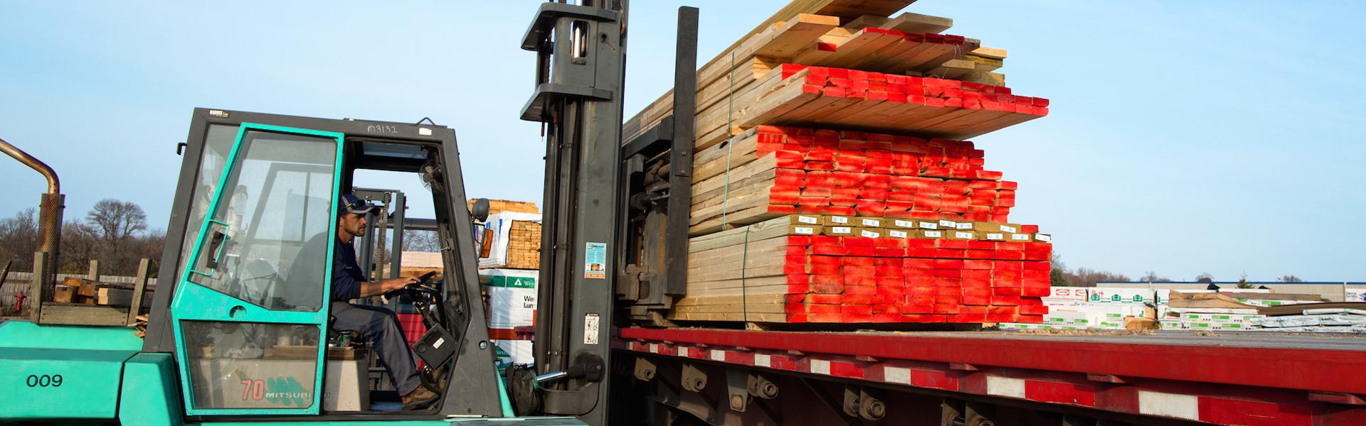 Lampert Lumber forklift loading a longbed Lampert Lumber Truck