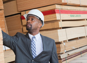 young male professional inspecting a lumber yard in suit and hard hat-10-25